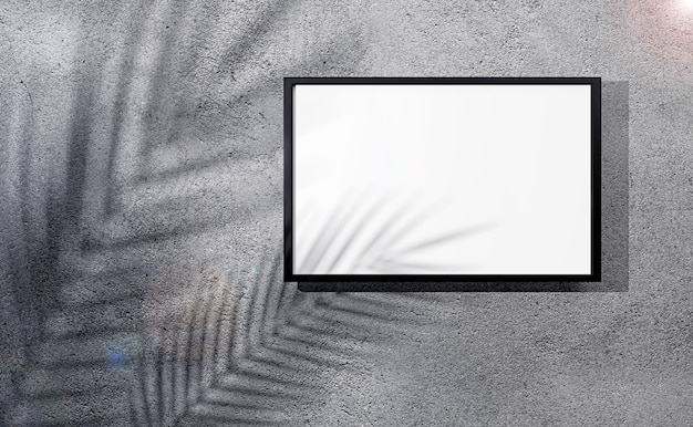 Blank photo frame on gray plastered wall with shadow of palm leaves.
