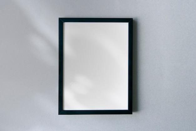 표면에 꽃 그림자와 햇빛이 있는 빈 사진 프레임 모형. 텍스트를 위한 공간이 있는 템플릿입니다.