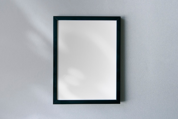 Blank photo frame mockup with floral shadows and sunlight on surface. template with space for text.