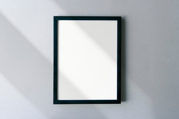 Blank photo frame mockup with shadows and sunlight on surface. template with space for text.