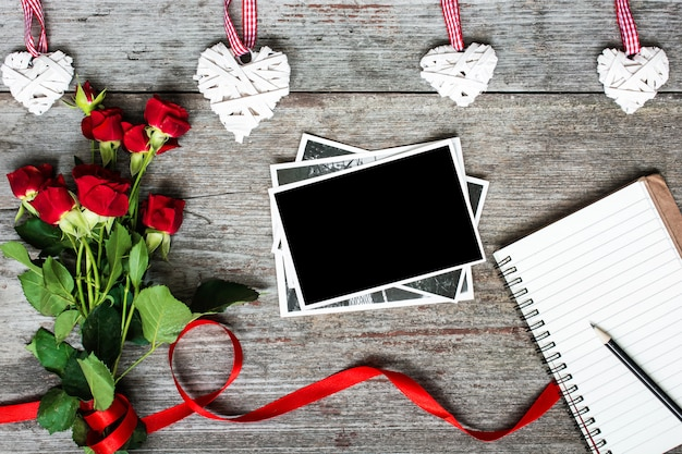 Blank photo frame and notebook with red roses and handmade wooden hearts