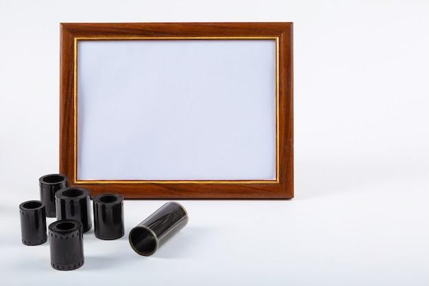 Пустая рамка для фотографий, фотопленка на столе.