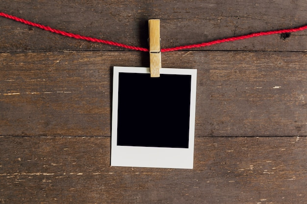 Blank photo frame with clothesline hanging on wood background.