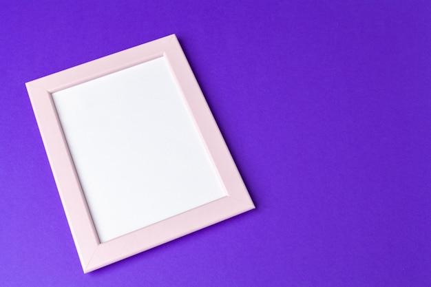 紫色の背景にコピースペースを持つ空白のフォトフレーム
