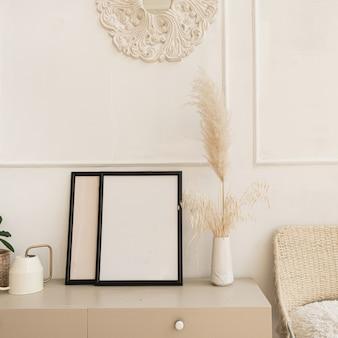테이블에 복사 공간을 가진 빈 사진 프레임입니다. 푹신한 갈대, 팜파스 잔디 꽃다발, 가정 식물, 흰 벽에 등나무 의자.