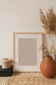 Blank photo frame with copy space, reeds bouquet in vase, rye in clay pot at white wall. modern interior design concept.