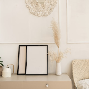 Blank photo frame with copy space on table. fluffy reeds, pampas grass bouquet, home plant, rattan chair against white wall.