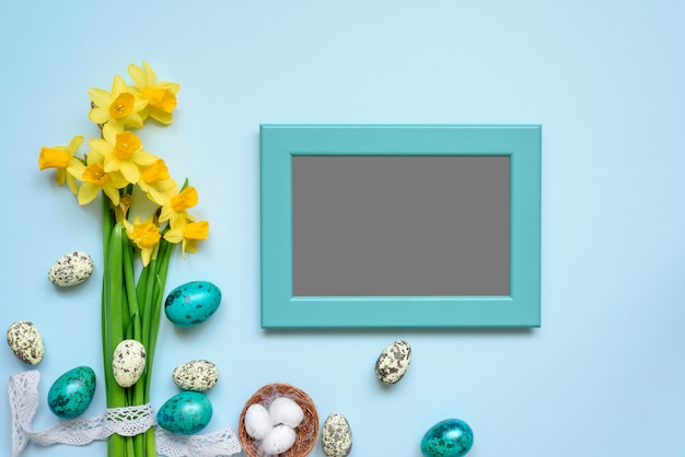 Blank photo frame with easter eggs and spring flowers. top view