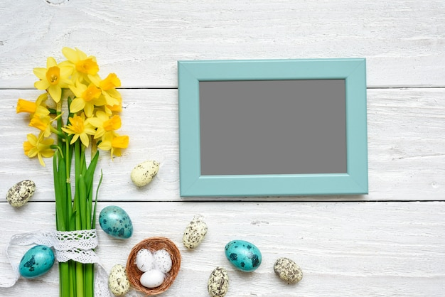 Blank photo frame with easter eggs and spring flowers