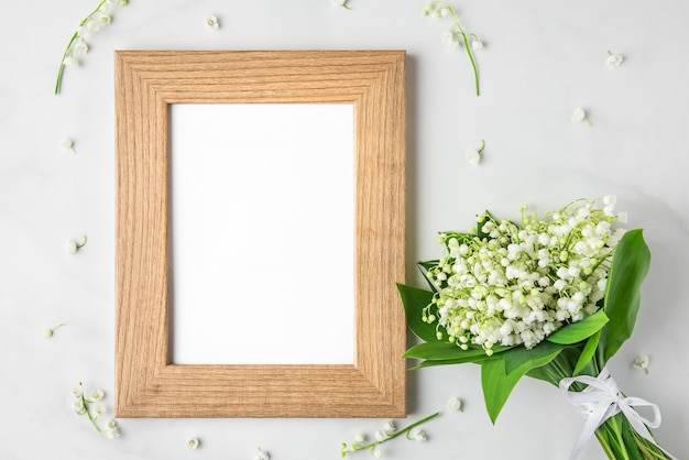 Blank photo frame with lily of the valley flowers bouquet on white. flat lay. top view