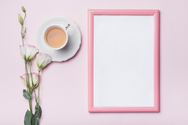 Blank photo frame with pink border; cup of tea and fresh eustoma flowers against colored background