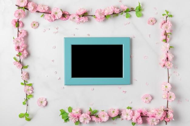 白い大理石の背景にピンクの花と空白のフォトフレーム。女性の日、母の日、バレンタインデー、結婚式のコンセプト。フラットレイ、モックアップ。コピースペースのある上面図