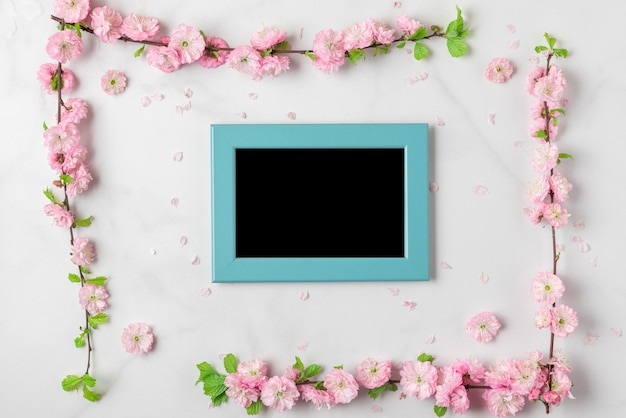 Blank photo frame with pink flowers on white marble background. womens day, mothers day, valentines day, wedding concept. flat lay, mock up. top view with copy space
