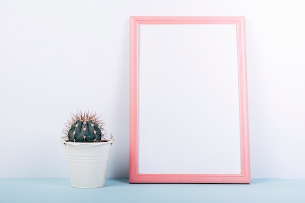 Blank photo frame with small succulent potted plant on blue table