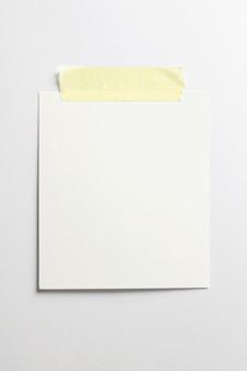 부드러운 그림자와 흰 종이 배경에 고립 된 노란색 스카치 테이프로 빈 폴라로이드 사진 프레임