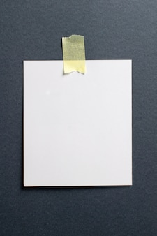 Blank photo frame with soft shadows and yellow scotch tape on black craft paper background