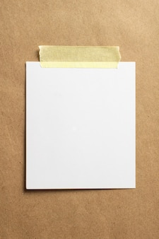 Blank photo frame with soft shadows and yellow scotch tape on craft cardboard paper background