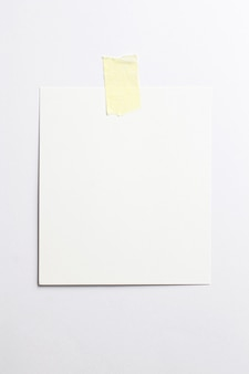 Blank photo frame with soft shadows and yellow scotch tape isolated on white paper background