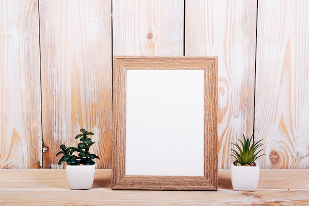 Blank photo frame with two succulent plants besides over wooden table