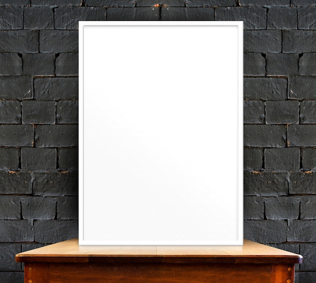 Blank photo frame on wood table at black brick wall,perspective background