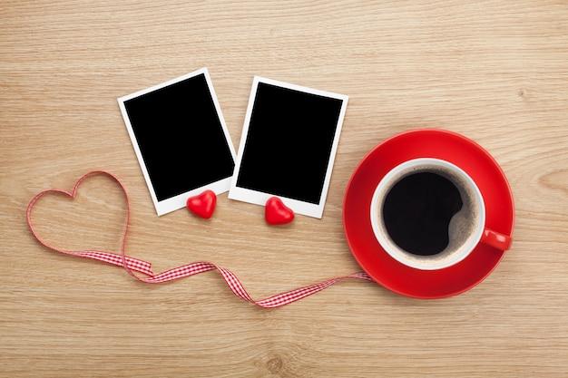 空白のフォトフレームと木製の背景の上の赤いコーヒーカップ