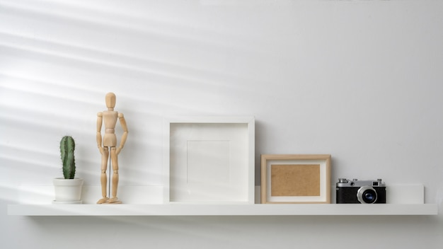 Blank photo frames, camera and decorations on white shelf with white wall