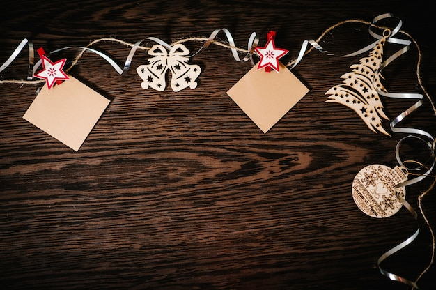 Blank, photo, instant, small paper hanging. christmas tree ornaments with ribbons, snowflakes, bells on brown, structural wood background. flat lay. top view, frame with space for text. happy holidays