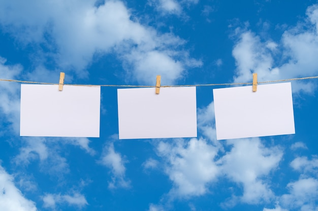 Blank photo paper hanging on a clothesline over clouds in the blue sky background