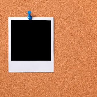 Blank photo pinned to a cork board