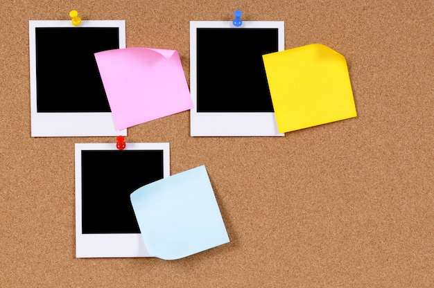 Blank photo prints with sticky notes pinned to a cork bulletin board.