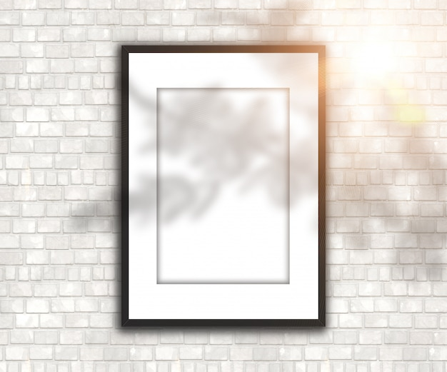 Blank picture frame on brick wall with shadow and sunshine