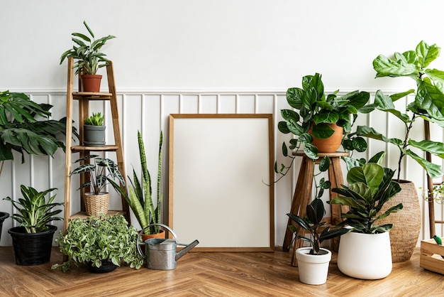 Blank picture frame by a houseplant corner on a parquet floor