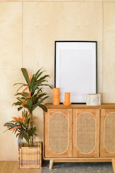 Blank picture frame on the furniture with candles and a plant on light wood wall background