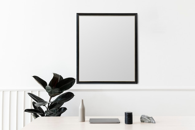 Blank picture frame hanging on a white wall