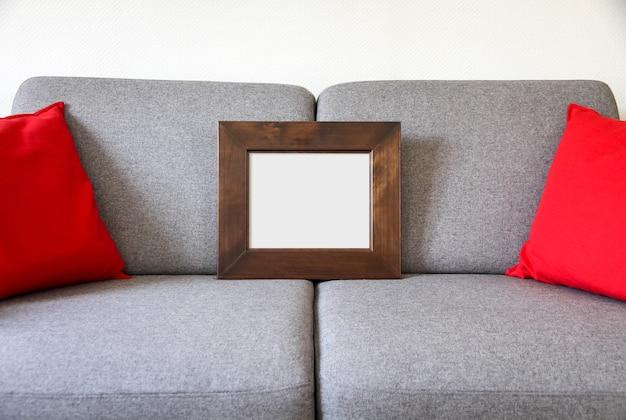 ソファの上の空白の額縁。ミニマリストのインテリアの背景