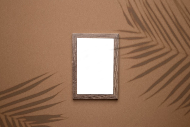 Blank picture frame on trend brown background with tropical plant shadow light as template for event promotion, design presentation, self portfolio etc top view