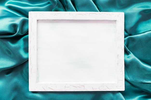 Blank picture frame on turquoise satin fabric