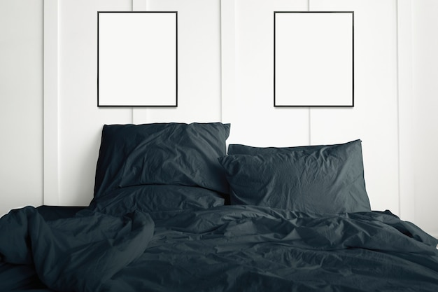 Blank picture frames hanging above a dark green bed