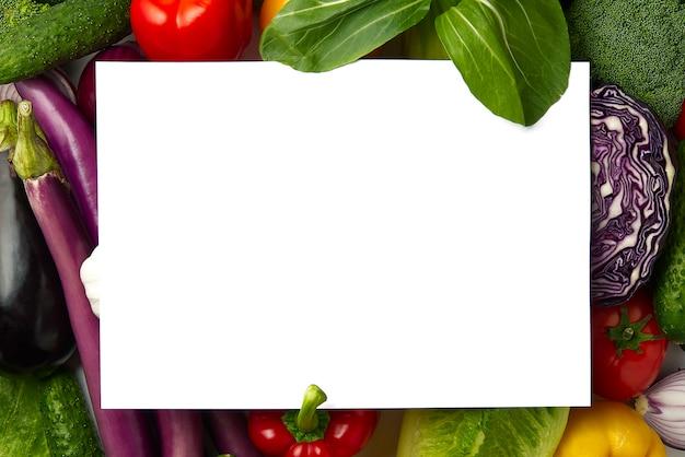空白の紙は、さまざまな種類の野菜の野菜レイアウトの上に横たわっています。