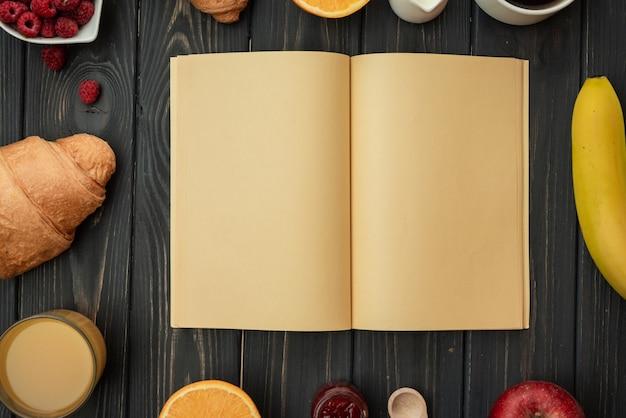 木製のテーブルの上の白紙。おいしい朝食、クロワッサン、コーヒー、ジュース、ラズベリー。