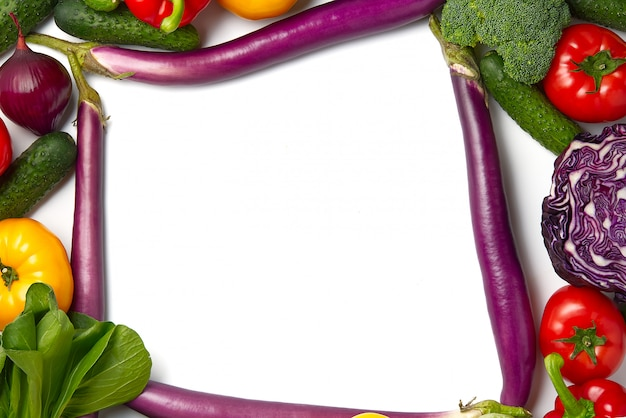 Blank piece of paper is lying on a vegetables layout with different kinds of vegetables.