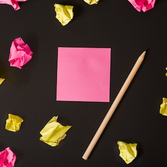 Blank pink adhesive note and pencil surrounded with crumpled paper on black background