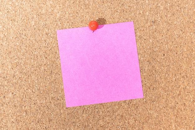 Пустое розовое примечание и канцелярская кнопка на пробковой доске. шаблон для текста объявления или рисунков
