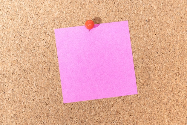 Blank pink note and push pin on cork board. template to ad text or drawings