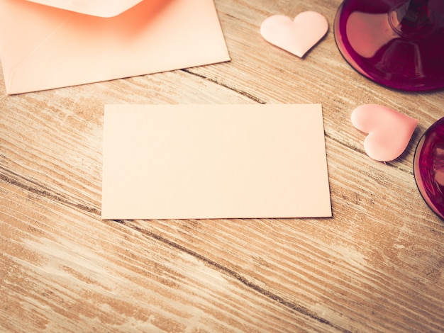 Blank pink paper letter note with hearts to fill with your text on wooden textured.
