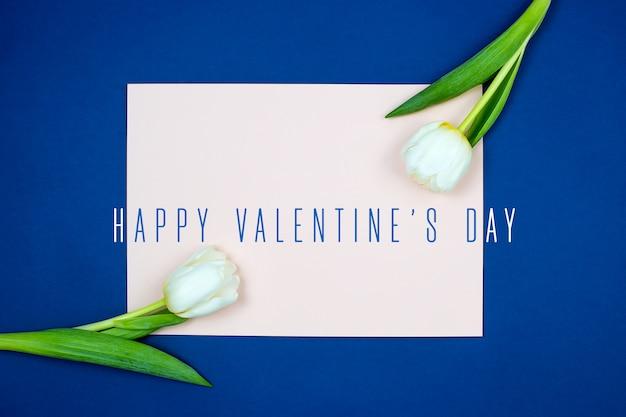 Чистый лист розовой бумаги и свежие цветы тюльпана с зелеными листьями на синем фоне, вид сверху
