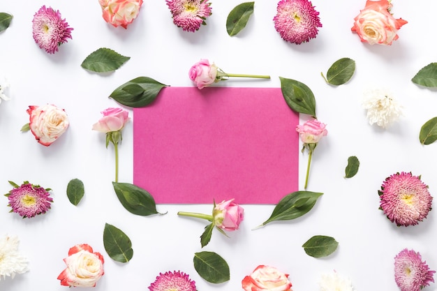 Blank pink paper surrounded by green leaves and flowers on white surface