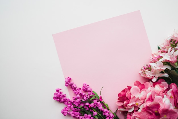Blank pink paper with colorful flowers on white background