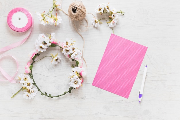 Blank pink paper with flower wreath; ribbon and spool on textured background