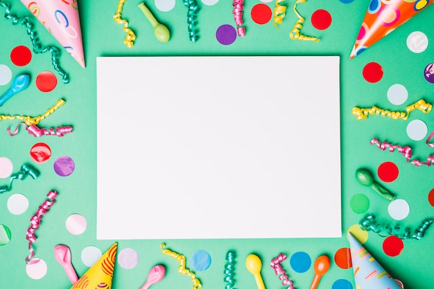 Blank placard decorated with birthday items on green background
